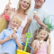 Family at beach with ice cream cones smiling — Stockfoto