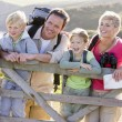 Family on cliffside path leaning on fence and smiling — Stock Photo #4771170