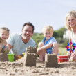 Family on beach making sand castles smiling - Photo