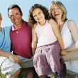 Family on fence outdoors smiling — Stock Photo