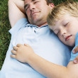 Father and son lying outdoors sleeping — Stock Photo