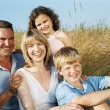 Family sitting outdoors smiling — Stock Photo #4771203