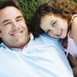 Father and daughter lying outdoors smiling — Stock Photo #4771227