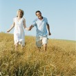 Couple walking outdoors holding hands smiling — Stockfoto