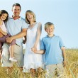 Family standing outdoors holding hands smiling - Stock Photo