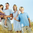 Family standing outdoors holding hands smiling — Stock Photo #4771232