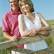 Couple standing outdoors by fence smiling — Stock Photo