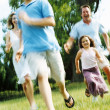 Family running outdoors smiling — Stock Photo