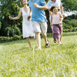 Family running outdoors smiling — Stok Fotoğraf #4771242