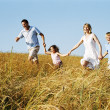 Family running outdoors holding hands smiling — Stock Photo