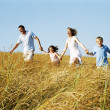 Family running outdoors holding hands smiling — Stock Photo #4771247