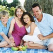 Family sitting outdoors with picnic smiling — Stock Photo #4771251