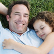Father and sleeping daughter lying outdoors smiling — Stock Photo