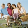 Family outdoors by fence with picnic basket smiling — Stock Photo