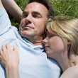 Couple lying outdoors sleeping - Stock Photo