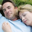 Couple lying outdoors sleeping - Lizenzfreies Foto