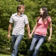 Couple walking outdoors holding hands smiling — Stock Photo