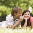 Couple lying outdoors with flower smiling — Stock Photo