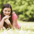 Woman lying outdoors with flower smiling — Stock Photo