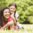 Mother and daughter lying outdoors smiling — Stock Photo #4771302