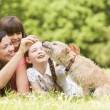 Stock Photo: Mother and daughters in park with dog smiling