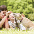Mother and daughters in park with dog smiling — Stock Photo