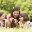 Mother and daughters lying outdoors with flowers smiling — Stok Fotoğraf #4771308
