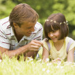 Father and daughter lying outdoors with flowers smiling - Stockfoto