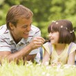 Father and daughter lying outdoors with flowers smiling — Stock Photo