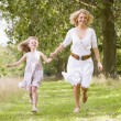Mother and daughter walking on path holding hands smiling — Stock Photo
