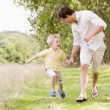 Father and son running on path holding hands smiling — Stock Photo