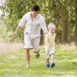 Father and son running on path smiling — Stock Photo