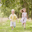 Royalty-Free Stock Photo: Two young children running on path smiling