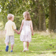 Two young children walking on path holding hands — ストック写真