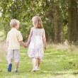 Two young children walking on path holding hands - Stock Photo