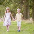 Two young children walking on path holding hands smiling — ストック写真