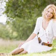 Woman sitting outdoors smiling — Stock Photo