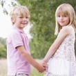 Two young children standing outdoors holding hands smiling — Stock Photo