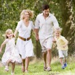 Family running on path holding hands smiling — Stock Photo