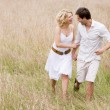 Couple walking outdoors holding hands smiling — Foto Stock