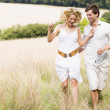 Couple running outdoors smiling — Stock Photo