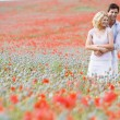 Couple in poppy field embracing and smiling - Stock Photo