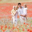 Family standing in poppy field smiling — Stock Photo