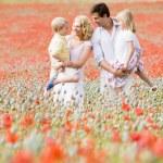 Family standing in poppy field smiling — Stock Photo