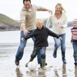 Family playing soccer at beach smiling — Stock Photo