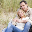 Couple sitting on beach smiling — Stock Photo #4771487