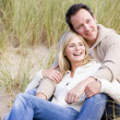 Couple sitting on beach smiling - Stockfoto