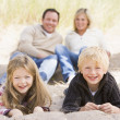 Family relaxing on beach smiling — Stock Photo