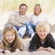 Family relaxing on beach smiling - Stock fotografie