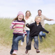 Family running on beach smiling - Stock fotografie